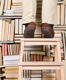 Man up on ladder against wall of books