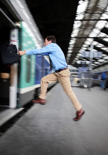 Businessman jumping to make a train